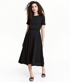 Black. Knee-length, short-sleeved dress in cotton jersey. Cut-out section at back with snap fasteners at top. Elasticized seam at waist and circle skirt.
