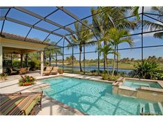 Tropical pool and spa - lake view - screened lanai - palm trees.  Grey Oaks in Naples, FL