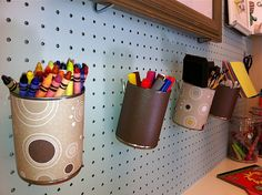 Use old cans covered in scrapbook paper to hold craft supplies on pegboard.