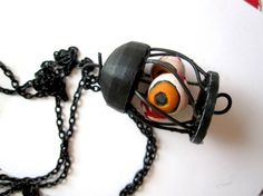 Three Orange Eyeballs in a Wire Cage Halloween Pendant by Untimed, $28.00