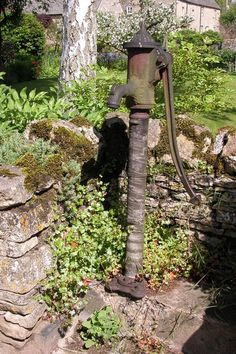 Old water pump in the wall of a garden