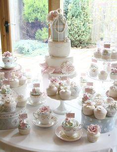 Lovely arrangement with hatboxes and teacups. Good close up of a rose on the cupcake for style ref