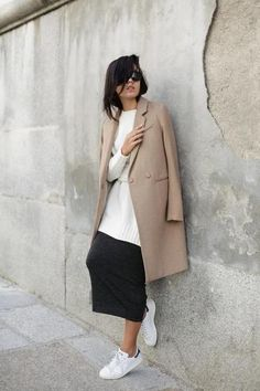 Winter Outfit Inspiration: Tan fall coat worn over a comfy white sweater, black midi skirt, and white Adidas sneakers.