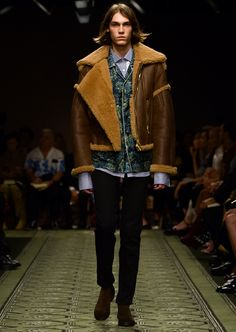 A sculptural shearling flight jacket worn over slim fit jeans and contrasting striped and floral shirts.