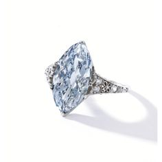 Platinum and Fancy Blue Diamond Ring, Tiffany & Co., Circa 1900 -  The modified marquise-shaped diamond of fancy blue color weighing 3.54 carats, within a delicate mounting set with old European-cut and single-cut diamonds weighing approximately .35 carat, size 3½, bearing partial signature 'T' for Tiffany & Co., two diamonds missing.