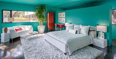 Eclectic Master Bedroom with Leather bedframe, Built-in bookshelf, can lights, White leather-look queen size bed, Paint in Dramatic color: Sherwin Williams Nifty Turquoise