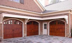 Real wood garage doors with arch windows handles and hinges. See more at www.ontracdoors.com