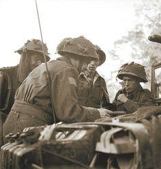 Personnel of Canada's North Shore Regiment consulting a map before launching an attack across the Orne River, July 16, 1944 | Des membres du régiment North Shore consultent une carte avant de lancer une attaque de l'autre côté du fleuve de l'Orne, 16 juillet