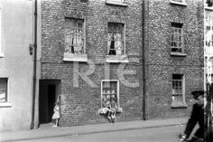 Children outside houses on Marrowbone Lane, Dublin city, in 1952 or 1953. A man on a bicycle is partly visible on the right. *Note the area of negative damage on the right of frame.* Collection RTÉ Johnson Collection Photographer Johnson, Nevill