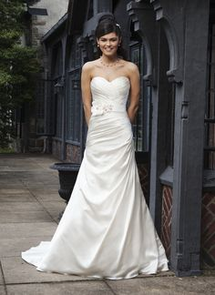 Sincerity wedding dress style 3725 An asymmetric pleated satin A-line gown with a pleated sweetheart  neckline. Buttons cover the zipper and this style has a chapel length  train. Comes with a detachable belt with flowers and beading.