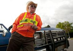 Crossing guard Merrill Gould, while leaning against his 1993 Dodge Ram truck, talks about his 12 years helping students cross roadways at schools. (Photo by John Zsiray)