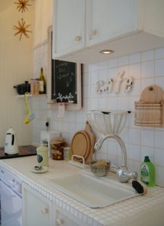 Miniature Kitchen by Yuri Munakata-inspiration for AG doll kitchens, tiles from Michaels, create countertop, soap dish painted white with acrylic paint, costco mini lights, create blackboard, hang untensils from small cup hooks, paint utensils silver