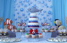 Olha que painel de fundo incrível para uma festa de fundo do mar. as bolas de isopor foram pintadas desiguais para parecer com bolhas de ar. Os bonecos de feltro em forma de peixe e tubarão ficam ainda mais fofos nessa mesa do bolo para aniversário de menino. Fabiana Moura - Projetos Personalizados