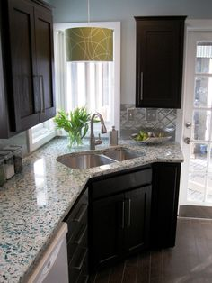 These recycled glass counter tops look great, and the stainless steel back splash, which I would normally  find too utilitarian, looks great in this warm and well lit space. (from Budget-Friendly Before-and-After Kitchen Makeovers : Home Improvement : DIY Network)