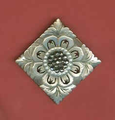 Pierced and carved shell button. Petaled flower with leaf motif at each corner. Center of the flower has small cut steels and a slightly larger cut steel pin shank.
