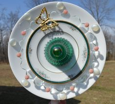 This piece starts with a plain white plate with clear glass petal plate.  Next is a vintage tea saucer and a candle holder that matches the rim and leaves in the pattern.  To top it off is a mini gazing ball.  The butterfly has landed on this beauty and is there to stay.  Accented with pearl glass stones and pink beads.  Butterflies are Free Glass Yard Art