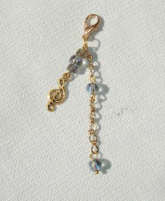 """This fashion charm features a clasp to attach it to about anything! Features quartz gemstone beads, labradorite gemstone beads, gold tone chain, and a music note charm! Measures 2.5"""" long. Makes a great gift!"""