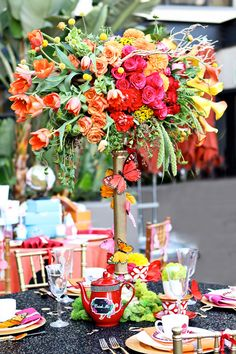 alice in wonderlandia party by hostess with the mostess bold bright color floral centerpiece design