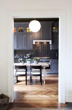 Kitchen with dark grey cabinets and black tile backsplash, round pendant light, and light hardwood floors. Classic Kitchen, New Kitchen, Kitchen Decor, Kitchen Furniture, Kitchen Trends, Kitchen Ideas, Grey Kitchens, Cool Kitchens, Kitchen Remodel