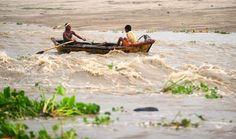 Dos habitantes cruzan un río de movimiento rápido en Allahabad, India. El monzón, que cubre el subcontinente de junio a septiembre, por lo general trae algunas inundaciones. Foto: AFP