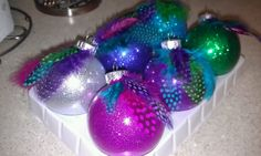 DIY Feather ornaments...Pour in mop and glo, shake it up and dump out, pour in glitter shake up and dump out...glue on feathers!!