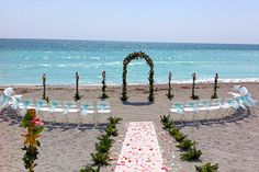 beach wedding arches and isle markers - wood use nicer wooden chairs maybe covered with sashes or not just florals on shephards hooks
