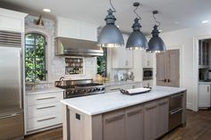 Beautiful kitchen features three black industrial pendants illuminating a long and narrow taupe center island fitted with stacked dishwasher drawers topped with white marble.