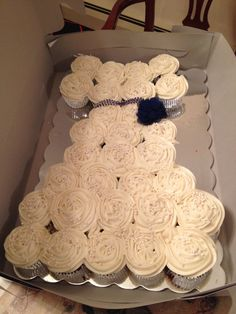 Wedding dress cupcake cake. Simple and adorable. 30 cupcakes (red velvet) with cream cheese frosting, blue string if crystals layered (non edible) and a decorative flower (also not edible)