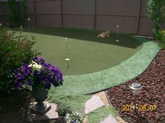 This artificial green is surrounded by a dark contrasting sea of decorative lava rock. The rocks, pathway, and putting green all have their own place thanks to edging. Picture compliments of a DIY homeowner.
