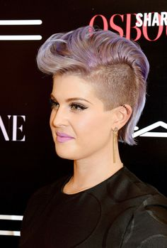 To promote her new makeup line with @M∙A∙C Cosmetics, Kelly Osbourne styled her hair in a mohawk look with matching lavender lipstick and winged eyeliner. #beautyhairstyles