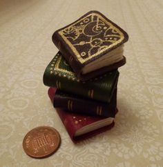 Nov 19th: Pile of miniature books so far with a penny for scale, including the Harry Potter House books and the Gallifreyan design. For the Design Every Day Project