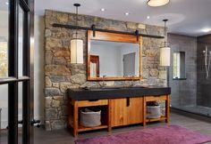 modern rustic bathroom design stone wall wood bathroom vanity with black countertop wood framed mirror purple rug gray tiled floors Unique Bathroom Mirrors, Rustic Bathroom Designs, Stone Bathroom, Modern Bathroom Design, Bath Design, Amazing Bathrooms, Bath Mirrors, Master Bathroom, Bathroom Ideas