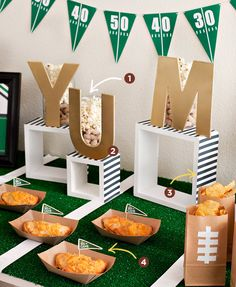 1. Fill glass cylinders or jars with popcorn and peanuts (in the shell) 2. Use chipboard letters spray painted gold to display themed messages 3. Make creative risers/stands from wall cubes + referee striped paper 4. Garnish your Cheeseburger Turnovers with mini pennant flags on toothpicks