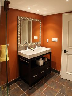 Half bath idea?  Warm terracotta walls, dark tile floor, dark wood vanity with clean angles.