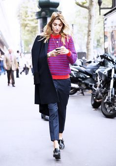 A red and blue crew-neck sweater is worn with black leather shoes, a black coat, and black trousers