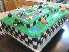 Photo 2 of 2. My oldest son's 5th birthday cake request. Mario Kart. This chocolate cake is two commercial full sheet cakes stacked on top of one another and a cake in the shape of the number 5 on top. Sides are marshmallow fondant as well as the Super Mario characters, road and water. The grass is piped buttercream. The only non-edible decorations are the pull back racers on the road. This 60 pound cake took a whooping 25 hours. But well worth it for Mama's #1 customer!