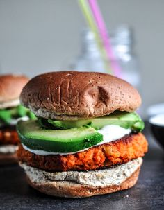 Smoky chicken burgers with roasted garlic cream and avocado.