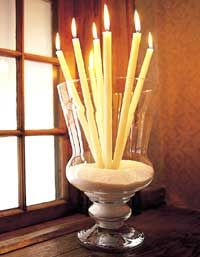 Instead of standing candles solo in soldier-straight rows, casually group them like fresh-cut flowers in a vase.