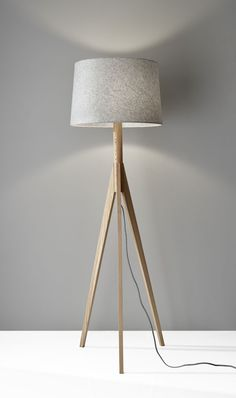 The beauty of the Edith Floor Lamp lies in the materials. A natural ash wood grain composes the tripod base of this lamp and is offset by a textured gray felt tapered drum shade. This simple and rusti Wood Floor Lamp, White Floor Lamp, Modern Floor Lamps, Wooden Tripod Floor Lamp, Rustic Floor Lamps, Modern Table, Modern Lighting, Lighting Ideas, Grey Wood Floors