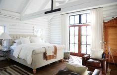 White Hot Home in Sonoma. Very rustic style bedroom in log cabin, white painted walls, lovely comfy bed with all-white linen