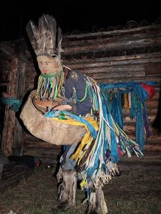 The shaman performing. His headdress had painted eyes. Eyes which see to the spirit world. Tassels conceal his own eyes.