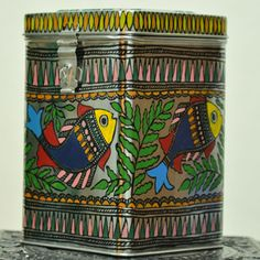 "Madhubani painted Tin Canaster- ideal for storage in the kitchen or other knick knacks.Beautiful, Unique & Durable - Madhubani painted Tin Canaster- ideal for bulk storage in the kitchen or linen or warm clothes .This art form depicts traditional stories painted by women on walls in Mithila, Bihar celebrating weddings, births and festivals. Size - 9""X6""X6"""