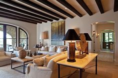 Wooden beams stained in a dark tone make this living room feel cozy, and add visual interest to the ceiling.