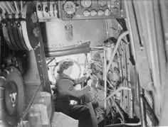 A WAAF electrician making an adjustment to the bomb switch units of a Lancaster bomber