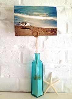 Lovely beach picture holder display idea with sand filled bottle or vase and wire holder.