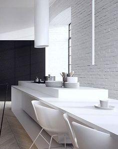 reforma cocina en vivienda rehabiitada, módulo central como isla y mesa de comedor, armario adicional color carbón, paredes ladrillo visto pintadas de blanco, suelo parquet en espiga.