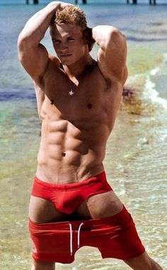In this Daily Package, Shawn Russell poses for DNA Magazine in two red swimsuits: a conservative one and one for only those that dare. Which do you prefer?