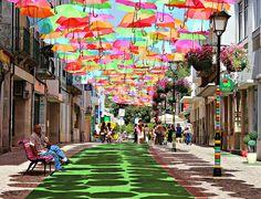 Fotografía: Calle con techo de sombrillas en Portugal.