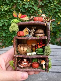 This beautiful fall fairy bookshelf will be a perfect addition to your collection. This miniature is filled with one of a kind handmade items, a tiny coffee pot, ceramic cup and saucer, real acorn caps, tiny pinecones, pumpkins and moss. I crafted the books, birds nest, basket of berries, and birdhouse myself with care and attention to detail. The shelf itself is an original, adorned with twigs, moss, leaves, faux mushrooms and grape vine curls. I also added a sweet butterfly and a tiny…