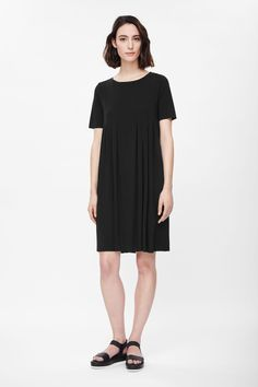 With folded pleats along the front, this dress is made from lightweight jersey with a subtle sheer quality and clean, raw-cut edges. A loose fit that flares slightly towards the hemline, it has a wide round neckline, in-seam side pockets and neat short sleeves.